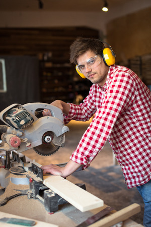master carpenter with headphones and glasses saws a board a circular saw machine, woodworking shop, the concept of a hobby, handmade Stock Photo