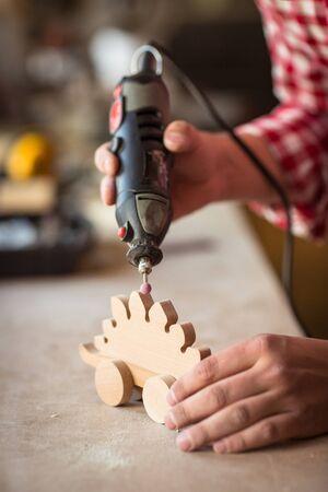 Craftsman lisser une surface de jouets en bois avec moud outils rotatifs, des outils et des copeaux de bois tout autour Banque d'images