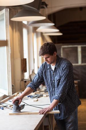 sander: Carpenter Using Electric Sander.