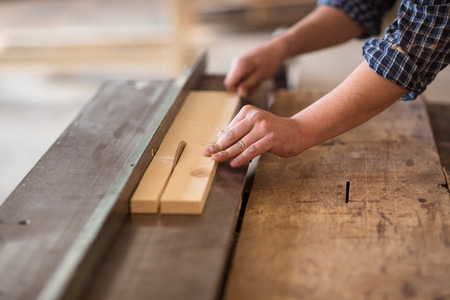 cut through: Skilled carpenter and small business owner working in his woodwork workshop, using a circular saw to cut through a wooden plank