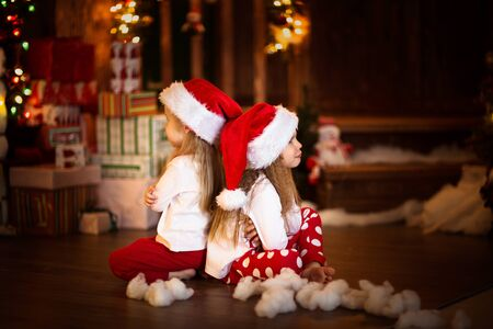 children girls offended to each other, Christmas tree, the concept of childhood, Christmas and New Year, on a dark background