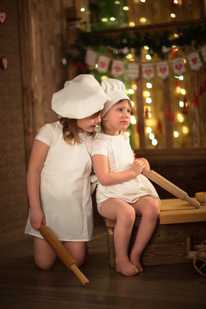 Girls cook with a rolling pin to stretch the dough, the concept of childhood, mothers helpers, independence. Dark background, lights Stock Photo