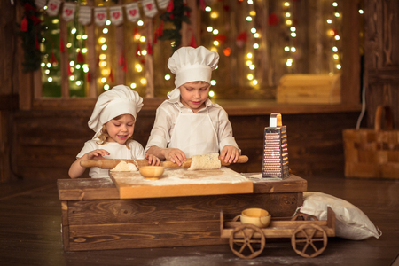 cook out: brother and sister baked, the dough is rolled out, the concept of mothers little helpers cook independence. Dark background, lights