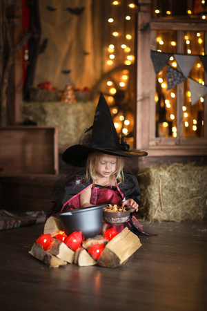 little witch in costum and hat conjure above pot, childhood halloween, dark background