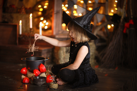 little Halloween  witch in costum and hat reading conjure above pot   childhood halloween, dark background Stock Photo