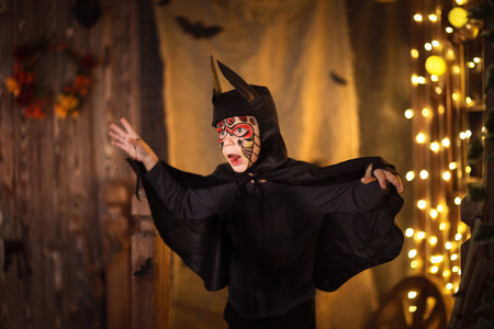 boys face painted   suit bat on  dark background,  mysterious childhood Stock Photo