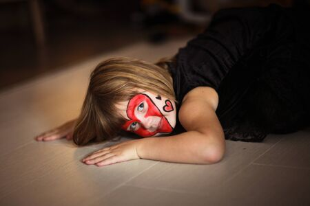 maquillaje infantil: niña de pintura de la cara sobre un fondo oscuro, el concepto de fiesta en el fondo oscuro