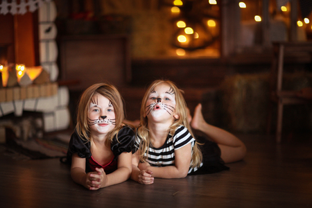 maquillaje infantil: face painting  girls cats on a dark background, the concept of  holiday Halloween  on  dark background