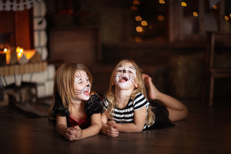 caritas pintadas: face painting  girls cats on a dark background, the concept of  holiday Halloween  on  dark background