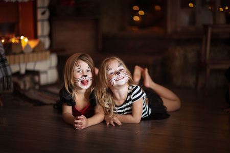 face painting: face painting  girls cats on a dark background, the concept of  holiday Halloween  on  dark background