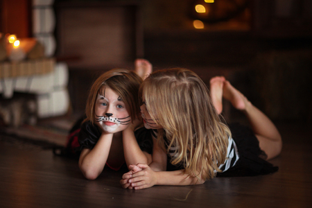 maquillaje infantil: pintura de la cara niñas gatos sobre un fondo oscuro, el concepto de fiesta de Halloween sobre fondo oscuro