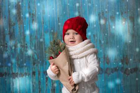 playful baby Toddler in bright hat with  bouquet of  fir branches on blue wood  background, lifestyle, concept Christmas and New Year