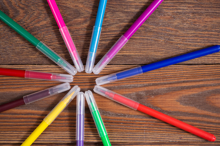 colored felt-tip pens on a wooden table background, the concept of creativity Rustic