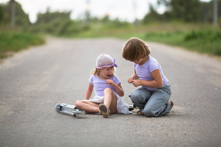 girl children scooter fell on the road In the countryside, sister helps her plaster on wound, child safety Stock Photo