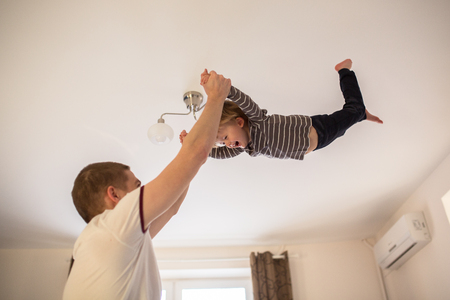 Dad plays with Toddler boy, tossing his son, a real interior, lifestyle, soft focus, fatherhood