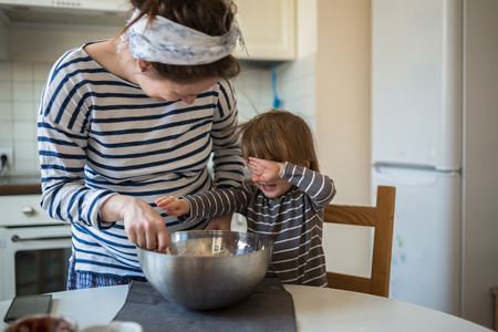 smiling young pregnant mother with dreadlocks is preparing in the kitchen with her son Toddler, make the dough for baking bread, lifestyle, toning, real interior Stock Photo