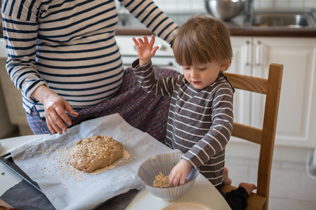 haciendo pan: Pregnant mom and making bread in the kitchen with her son Toddler, hands close-up, toning, real interior, lifestyle