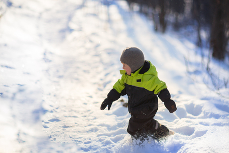 Toddler boy playing  outside in winter suit, snow falls