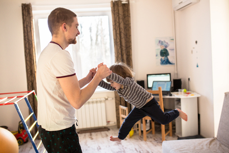 cradling: Dad plays with Toddler boy, tossing his son, a real interior, lifestyle, soft focus, fatherhood