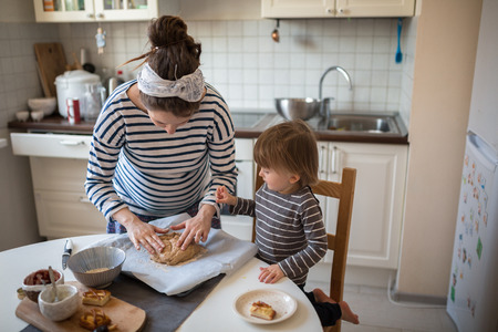 haciendo pan: young pregnant mother with dreadlocks making bread in the kitchen with her son Toddler toning, real interior