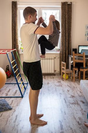 cradling: Dad rolls Toddler boy on the leg, a real interior, lifestyle, soft focus, fatherhood