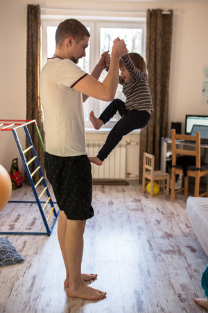 Dad rolls Toddler boy on the leg, a real interior, lifestyle, soft focus, fatherhood