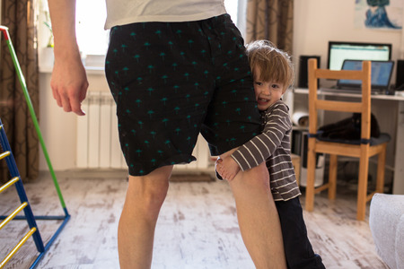 cradling: Dad rolls Toddler boy on the leg, a real interior, lifestyle, soft focus, fatherhood