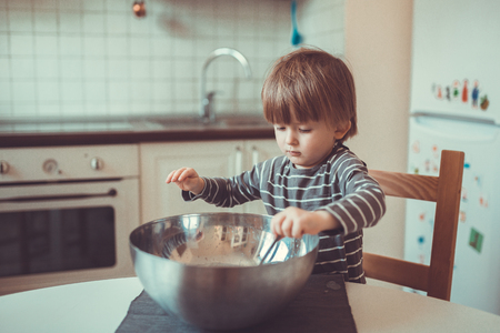 toddler boy: Toddler boy with a bowl in the kitchen making dough, childhood, real interior, toning, lifestyle, soft focus