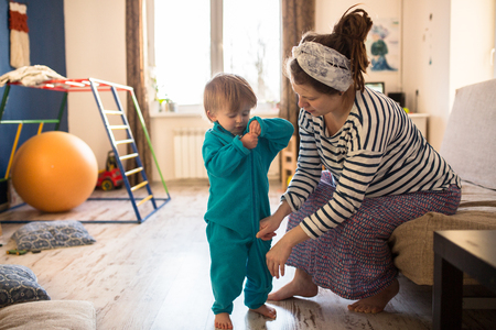 niños vistiendose: Mom puts her son, a boy Toddler clothes coveralls using mothers, the real interior, lifestyle, soft focus, fatherhood Foto de archivo