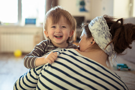rastas: Happy Toddler boy hugging his mother, close-up, feeling, the real interior, soft focus, light toning, concept and childhood dreams