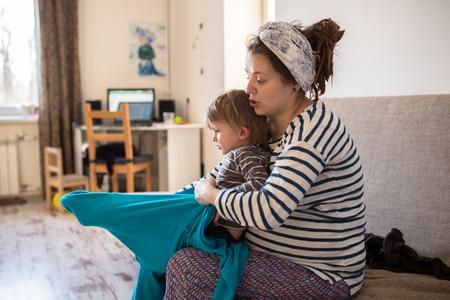 niños vistiendose: Madre pone a su hijo, un niño de la ropa del niño monos utilizando las madres, el interior de bienes, estilo de vida, enfoque suave, la paternidad