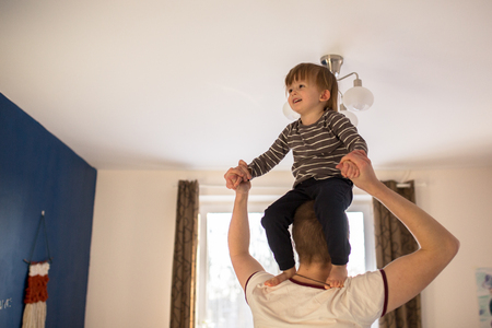 cradling: Dad plays with Toddler boy, is his son on his neck, a real interior, lifestyle, soft focus, fatherhood