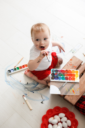 smutty: smutty kid Toddler with watercolor paints in red trousers on a light background,