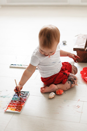 smutty: smutty kid Toddler paints watercolors eggs in red trousers on a light background, Stock Photo