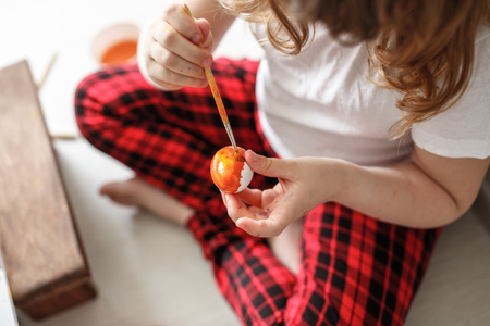 smutty: girl child paints watercolors eggs in red trousers on  light background,