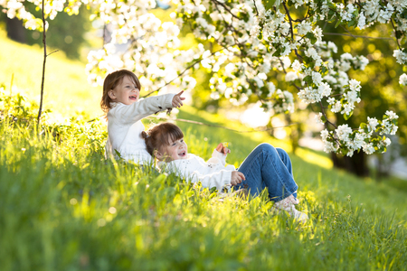 Delicate girls sisters hug around the branches of apple blossom, bright, sunny childhood, spring concept