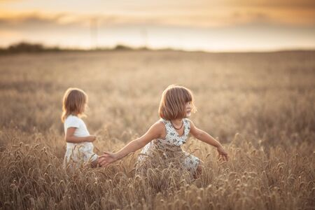 Two emotional sisters girls dance in the field with rye at sunset, happiness and freedom, lifestyle and selective focus