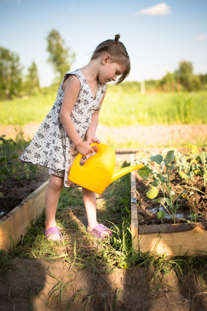 Fun baby girl watering seedlings from a watering can in the garden, kitchen garden Stock Photo