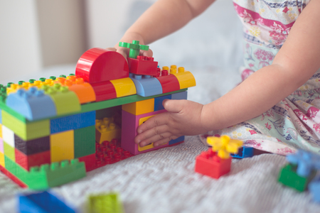 Toddler baby builds a house from a designer, close-up, lifestyle in a real interior, light background, toning