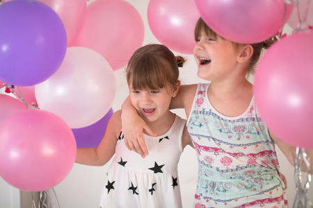 Sibling sisters children in dresses playing with balloons, concept happy childhood and holiday, lifestyle