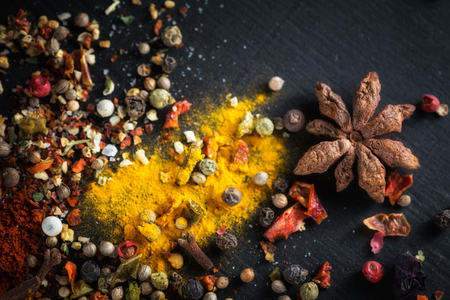 Cardamom, anise. Different colorful seasonings close-up against a black chalk board