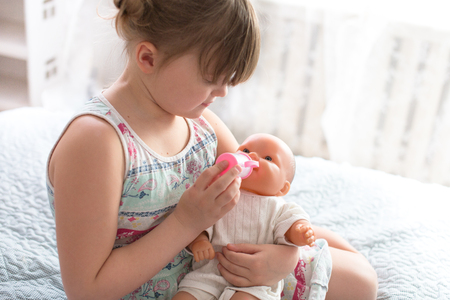 Kid girl playing with a doll, feeding a doll from a bottle, taking care of a doll, concept maternity, life style and childhood