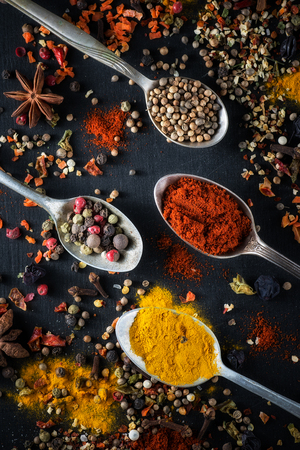 colorfully: Spoons with different colored spices on a black background chalkboard, Stock Photo