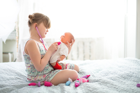 Kid girl playing with a doll, playing doctor with a stethoscope, taking care of a doll, concept maternity, lifestyle and childhood