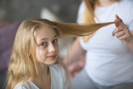 beautiful mother cares about a teenage daughter. Mom curls straightens hair to her daughter, Mom and daughter with long blond hair, concept of tenderness and care in real room Stock Photo