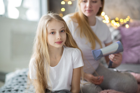 Beautiful mother takes care of her teenage daughter. Mother dries hair with a blow-dryer daughter. Mother and daughter with long blond hair,  concept of tenderness and mutual understanding