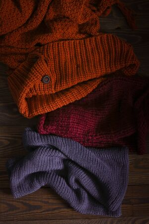 knitted scarves on a wooden background, the concept of autumn and warm clothes
