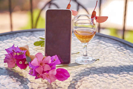 Mock up of mobile screen with glass of wine decorated with fresh bright summer surreal flowers. Feminine flat lay. Copy space. High quality photo Banque d'images