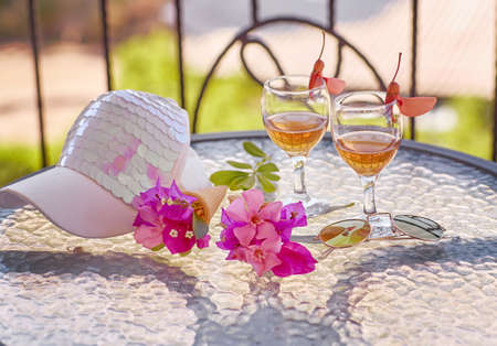 Summer homemade cocktails on bright green background with pink flowers of bougainvillea. Bright women cap. Summer starts creative concept. High quality photo
