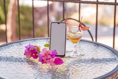 Mock up of mobile screen with glass of wine decorated with fresh bright summer surreal flowers. Feminine flat lay. Copy space. Summer mock up. High quality photo Banque d'images